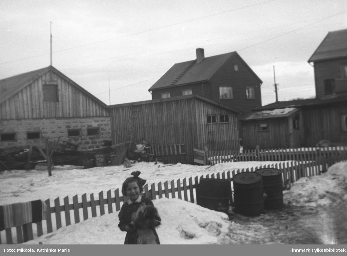 Lita jente i en hage i Kirkenes. Hun har bare på seg en kjole, og i armene har hun en filledukke eller et kosedyr. I bakgrunnen ser vi boliger og uthus, og ei matte henger til tørk på et gjerde. Bildet er antakelig tatt på vårparten, for snøen virker skitten og våt
