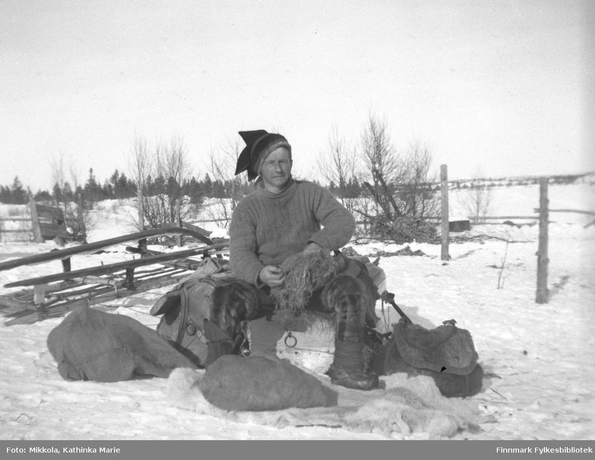 Jakob Hallonen i Pakanajoki, 1937. Han sitter utendørs på en hvelvet pulk, i bakgrunnen en hvelvet slede. Jakob er kledd i genser, stjerneluer, bellinger og skaller. Han har gress i fanget - dette kan være sennagress. Halvfulle sekker ligger i snøen rundt ham