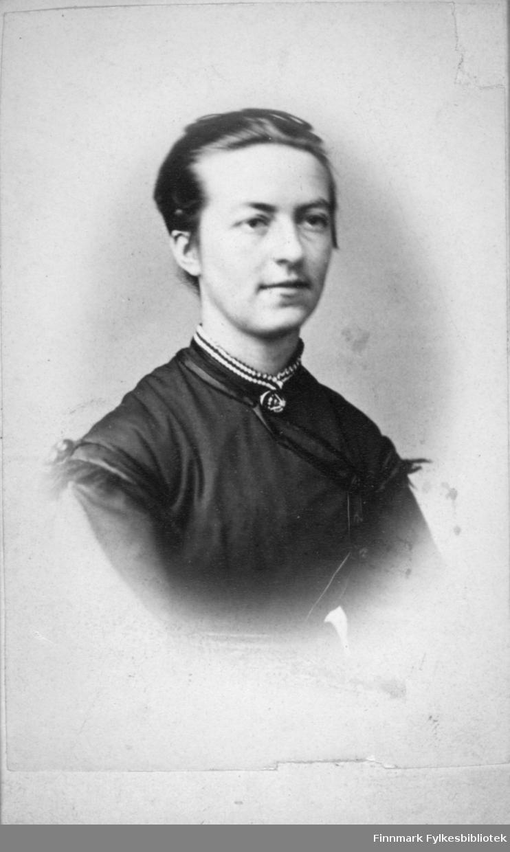 Portrett av en dame med kort, bakovergreid hår. Hun har en mørk bluse på seg og et smykke rundt halsen. Portrettet er tatt hos H. Ulseth i Bergen.