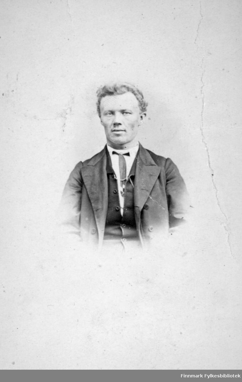 Portrett av en mann. Han har mørk dressjakke, mørk vest under, hvit skjorte og slips. Portrettet er tatt hos fotograf M. Koefoed.