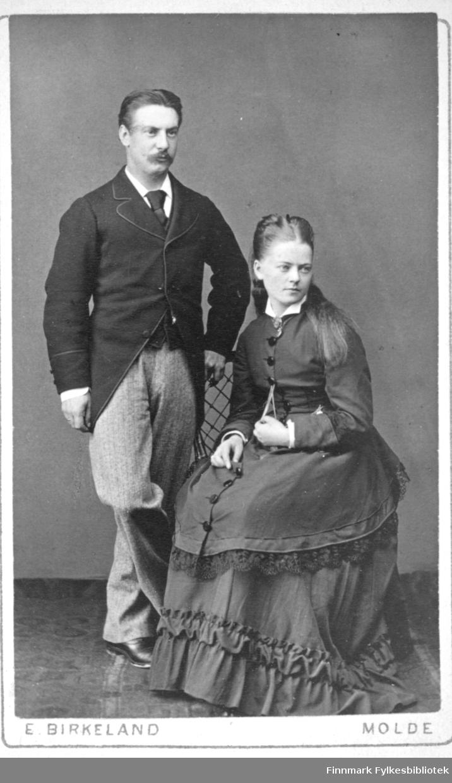 Portrett av en dame og en mann. Damen har en sid, mørk kjole og sitter i en stol. Mannen står ved siden av iført mørk dressjakke, hvit skjorte med slips og en ganske lys dressbukse. Portrettet er tatt ved E. Birkeland atelier i Molde.