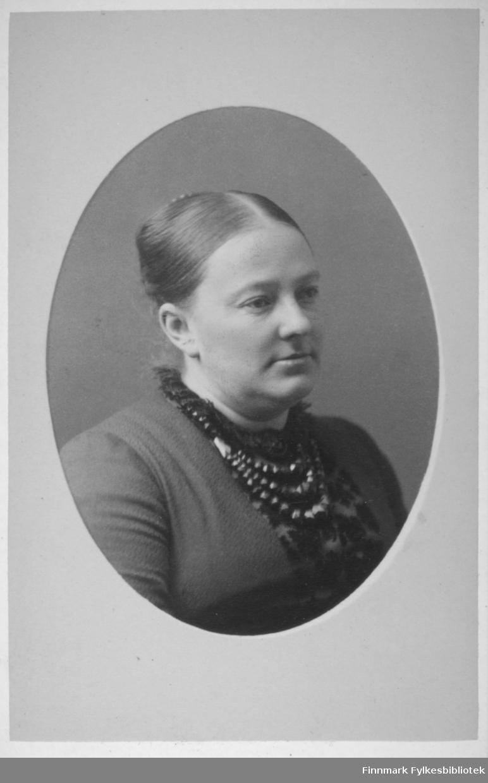 Portrett av en dame iført en mørk, tynn genser. Et smykke henger rundt halsen hennes. Portrettet er tatt hos Frederik Klem i Christiania.