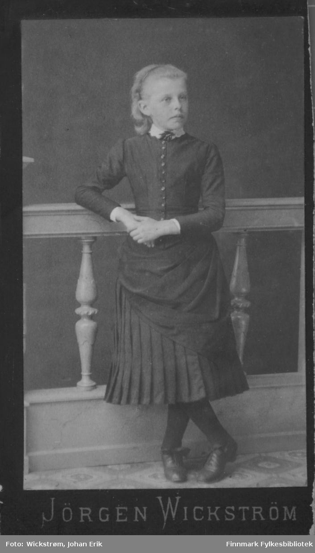Portrett av en ung jente. Hun har en mørk kjole, mørk strømpebukse og mørke sko på seg. Hun hviler høyrearmen på et rekkverk som har stolper med dreiemønster.