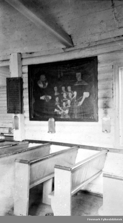 Et bilde/maleri av presten Gamst m.fl. henger på veggen i Loppa kirke. Veggene har liggende panel og både vegg- og takbjelker kan ses på bildet. En salmetavle henger helt til venstre og flere, små lysestaker henger på veggen. Kirkebenkene står på rekke og rad langs veggen. De er lyse med mørk handlist på toppen.