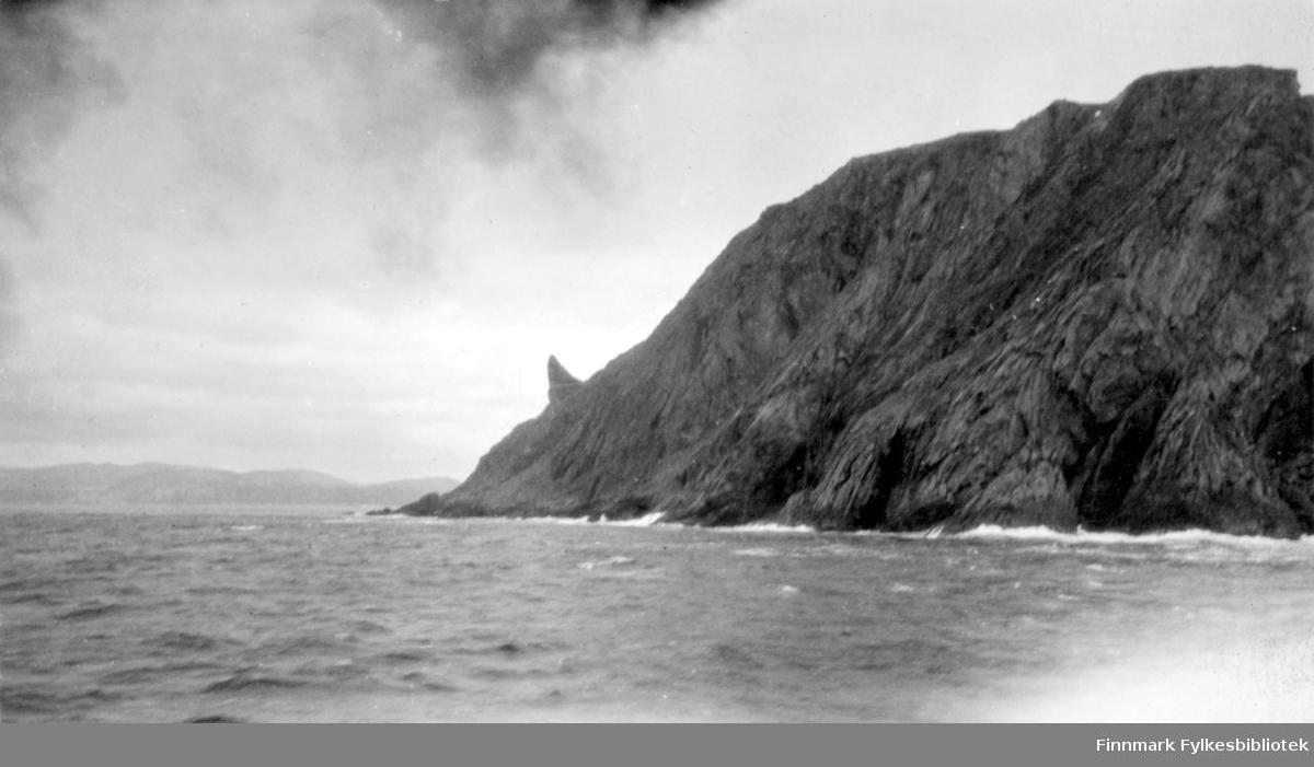 Nordkapphornet litt øst for Nordkapp ved fjellet Stor-Kappa. Noe vind med bølger på havet. Tungsjøen lager en skumstripe ved foten av fjellet. Svart røyk fra skorsteinen på båten ses øverst på bildet. Lengst i bakgrunnen ses Børnesfjellet.