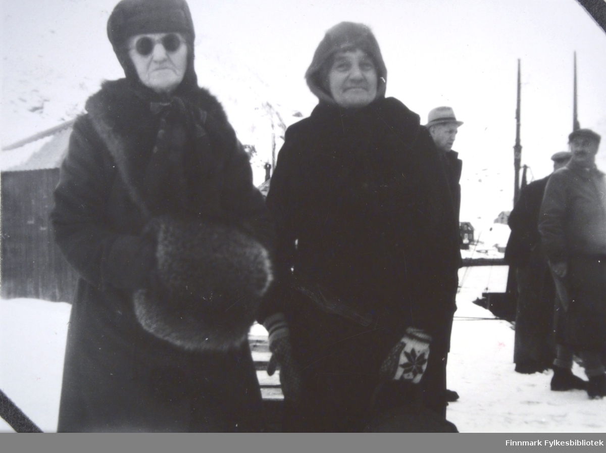 To eldre personer fotografert i et havneområde. Personen til venstre har en mørk kåpe/frakk med skinnkrave, lue med øreklaffer, vanter og et par solbriller på seg. Personene har også noe stort og loddent i hendene. Personen til høyre har en mørk kåpe/frakk, hette på hodet og strikkede vanter med mønster. Bak dem ser man det hattekledte hodet til en mann. Helt til høyre på bildet står en mann i mørke klær og sixpence på hodet. De to mastene med tauverk til en båt stikker opp til høyre på bildet. Kaia har et tynt snølag og en stor bygning står helt til venstre. En liten del av sjøen på havna ses mellom de to personene som står bakerst og over på andre siden er et snødekt område.