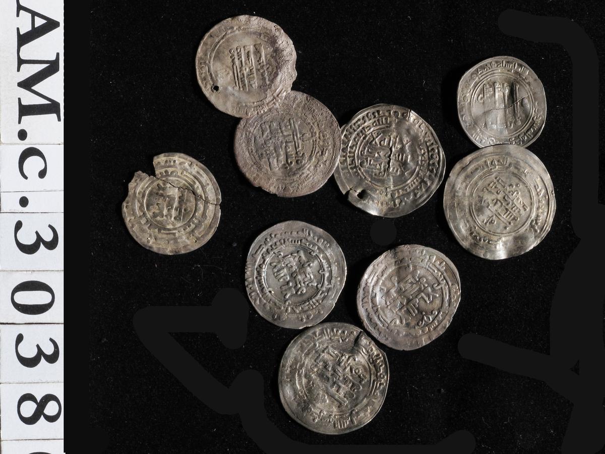 Ni arabiske sølvmynter (A. 357 i).Abbasider.  1) al-Muktafi. Suq-al-Ahwaz. 289 e.H. = 901/2. Jfr. NC 1919,s. 197. 3,18 g.Samanider.  2) Ahmad ibn Isma il.Samarqand. 301 e.H. = 913/14. Tbg. 202.3,04 g.  3) Ahmad ibn Isma il. as - Sas (Tasjkent). 301 e.H. Tbg. 200.2,74 g.  4) (Ahmad ibn Isma il. Samarqand. 295-301 e.H. = 902-07).Ettermynting. Perforert. 2,38 g.  5) Nasr ibn Ahmad. as - Sas. 308 e.H. = 920/1. Tbg. 293. 3,02 g.  6) Nasr ibn Ahmad. Andarabah. 310 e.H. = 922/3. Tbg. 329. 2,83 g.  7) Nasr ibn Ahmad. Samarqand. 310 e.H. = 922/3. Tbg. 322. 4,55 g.  8) Nasr ibn Ahmad. Samarqand. 314 e.H. = 926/7. Jfr. Tbg. 359 f. Ettermynting? Perforert. 3,50 g.  9) (Nasr ibn Ahmad, al - Muqtadir. Ca. 301-320 e.H. = 913-32).Ettermynting. I to deler, brutt ved opptagningen. Et litestykke mangler. 2,14 g.  Funnets nåv. samlede vekt: 327,727 g. Sølvgehalt: 800/1000 g.