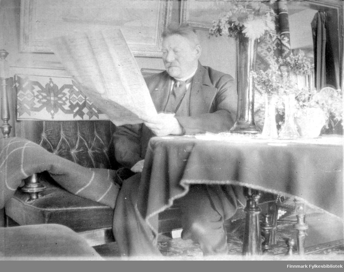 Arthur Buck sitter å leser i sofaen. Han holder en stor avis foran seg og er iført en ganske mørk dress, med hvit skjorte og slips. Sofaen han sitter i har litt mønster på sofaryggen. Et åkle eller et lite teppe henger over sofaryggen og et pledd ligger over armlenet. På veggen over sofaen henger et stort maleri. Det runde bordet som han lener armen på har heldekkende duk og blomstervaser i flere fasonger står oppå med blomster i. Et teppe ses såvidt på gulvet. Oppe til høyre på bildet er er døråpning med forheng trukket delvis tilbake.