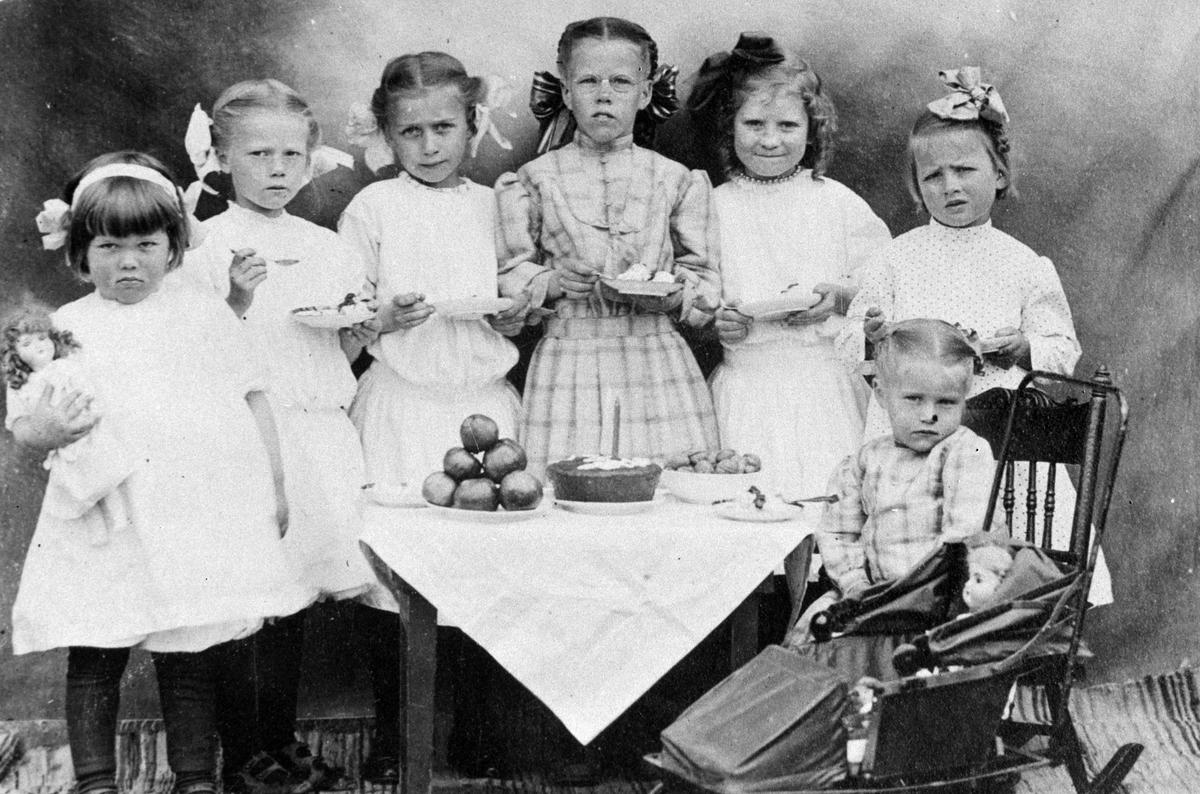 Amerikabilder, Per Mæhlum, Vallset. Gruppebilde, 7 personer, barn som spiser kake, barneselskap. Fra venstre Helene(ukjent etternavn), Selma Olsberg, Olva Olsberg, Dagny Mæhlum, Margaret abrahamsen, Ester Nordgård, foran til høyre Mildrid Mæhlum. Katheryn, Nord-Dakota, USA, ca 1911.