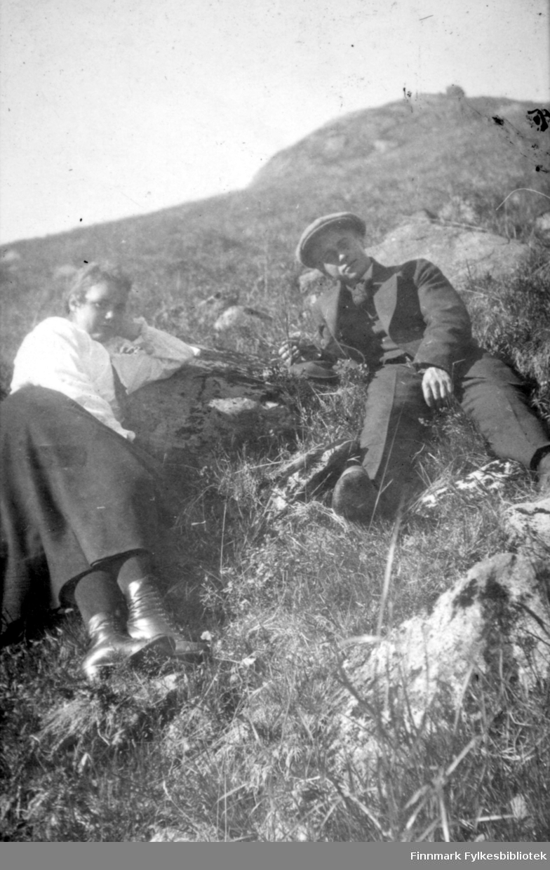 To personer sitter i en bratt fjellside. Toppen ses i bakgrunnen og en stor stein ligger der. Damen til venstre på bildet har et mørkt skjørt, hvit bluse og sorte sko på beina. Mannen til høyre har en mørk dress og sixpence på hodet. Det er mye gress der de sitter, men noen steiner ligger også i terrenget. Sola skinner og det ser ut til å være en flott sommerdag.