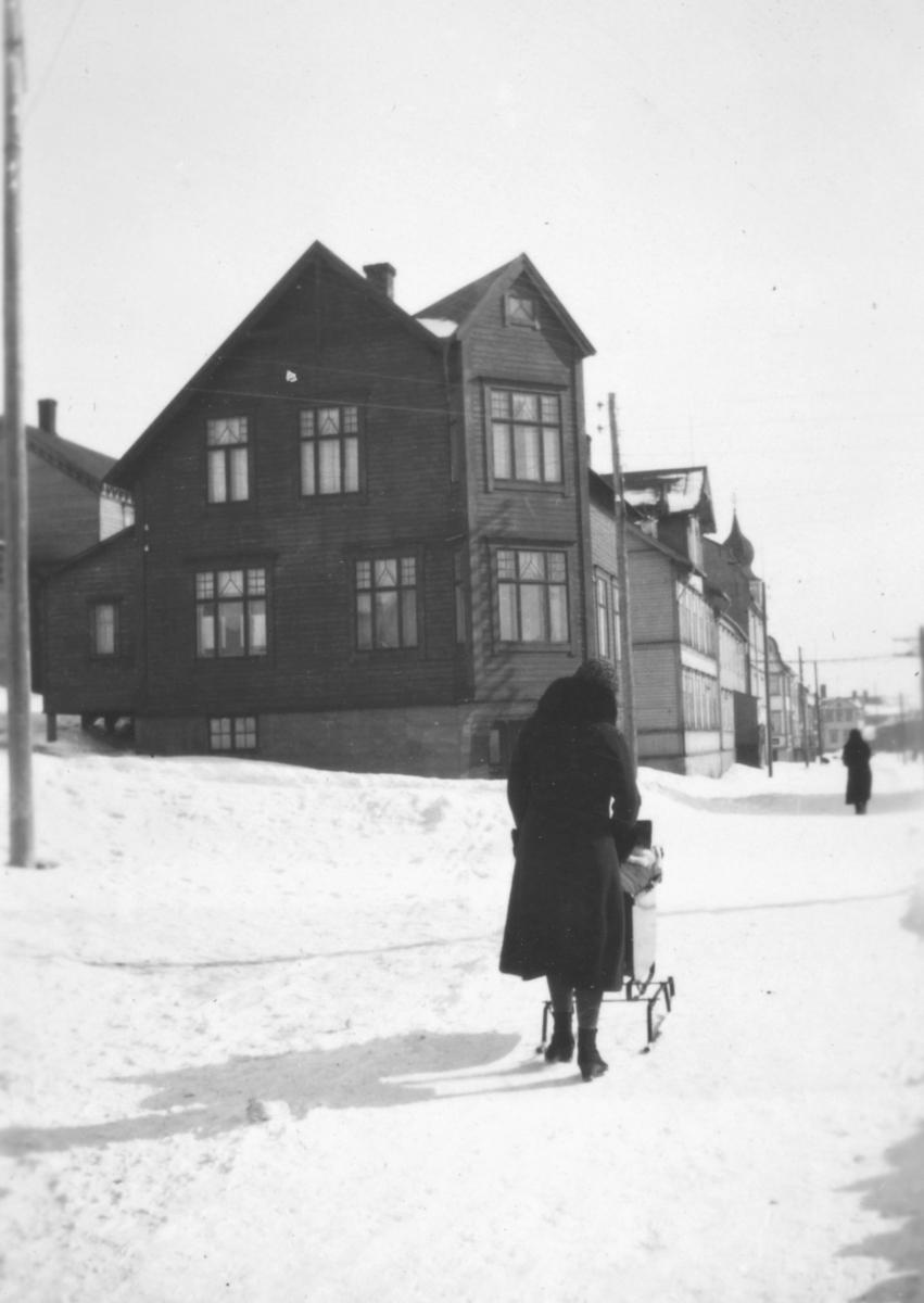 Vinteren 1934 i Havnegaten. Bildet et tatt fra omtrent der avisa 'Finnmarken' har sine lokaler. Rett frem ligger Sellstrømgården som Hauge familien flyttet til. Alfrida Hauge går på veien, med sønnen Tor Hauge i barnevogna.