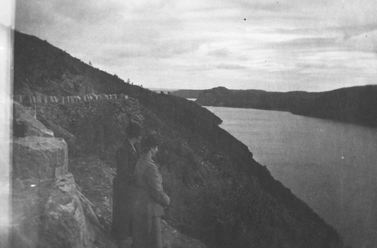 To kvinner som står og ser utover en elv, muligens er det Pasvikelva