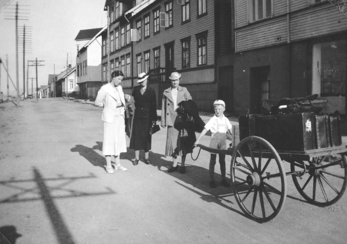 Tor Hauge står og holder skjekene på ei handvogn, med store hjul. Kvinnen i hvitt er hans mor Frida Hauge. De to andre damene er besøkende fra Bergen. Bildet er tatt i Havnegata