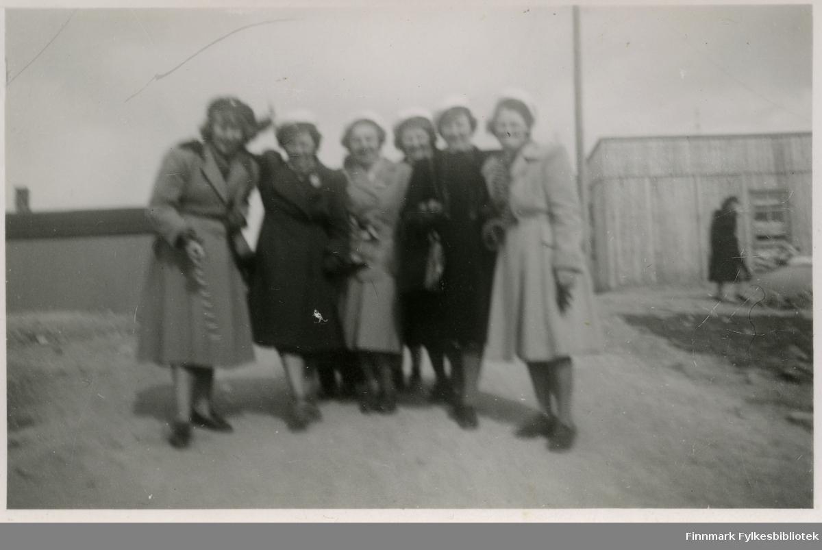 Medlemmer av Vadsø damekor poserer i gruppe. De har alle på seg en hvit hatt (trolig kor uniform)og kåper. Skoene er syndlige på alle. I bakgrunnen kan man se bebyggelse. Til høyre bak damene kan man se en kvinne. Ved kvinnen står det en stolpe.