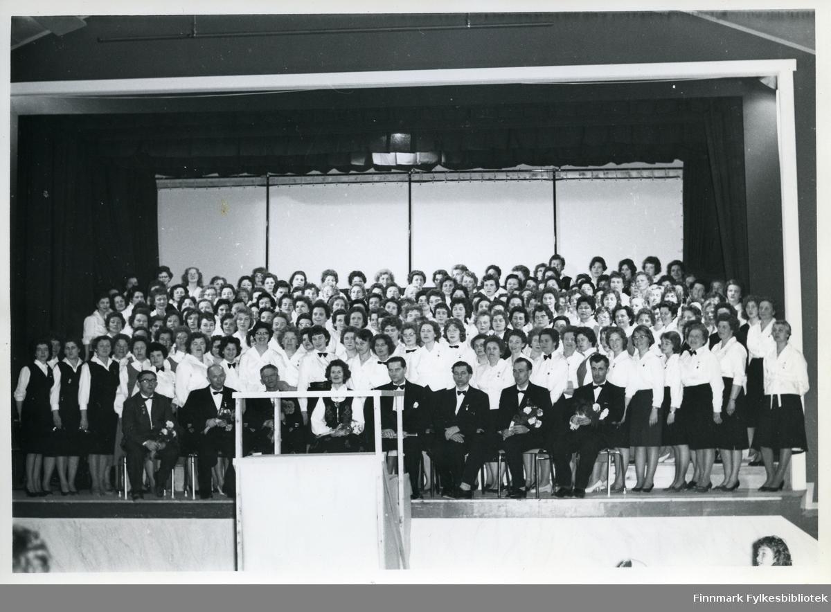 Felleskoret i Berlevåg med sine dirigenter 1962. Koret står oppstilt på en scene. De har alle uniformer på seg. Bak koret kan man se sceneteppet. Foran koret kan man se en talerpod. Kvinnene har på seg skjørt og skjorte. Mennene dress og sløyfe rundt halsen. Bak bildet er det notert: 'M.Z', for Mimmi Zahl.