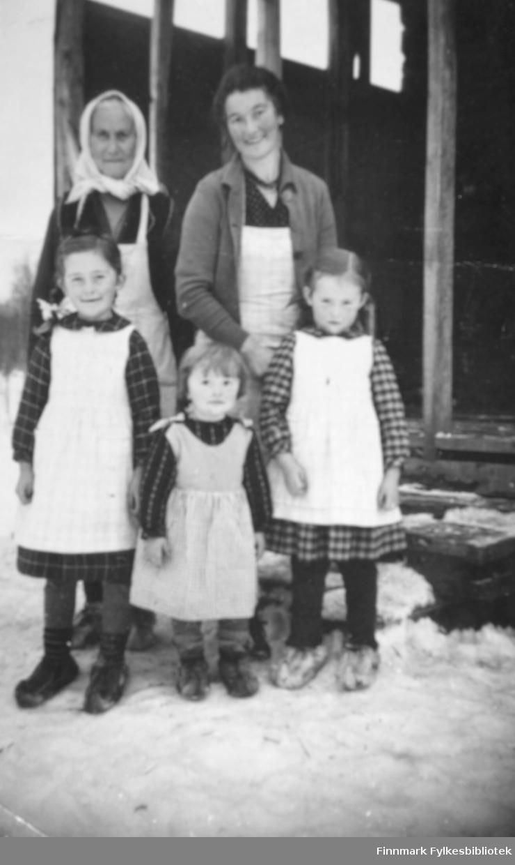 Karen Kristine Thomassen til venstre er tante til Karen Thomine Lovise Johansen f. Kristensen som står ved siden av, bak til høyre. Foran står barna henne. De tre søstrene er fra venstre: giver av bildene Karen Kristine Johansen g. Jakobsen, Anna Elisabeth Johansen g. Uglebakken, og Ragnhild Marie Johansen g. Suhr. Jentene er kledt i kjoler med hvite forklær over. På bena har de skaller. De voksne har også hvite forkle på seg. 'Moster' har ett hvitt tørkle på hodet. De står ute foran en trapp. Det ligger snø på bakken