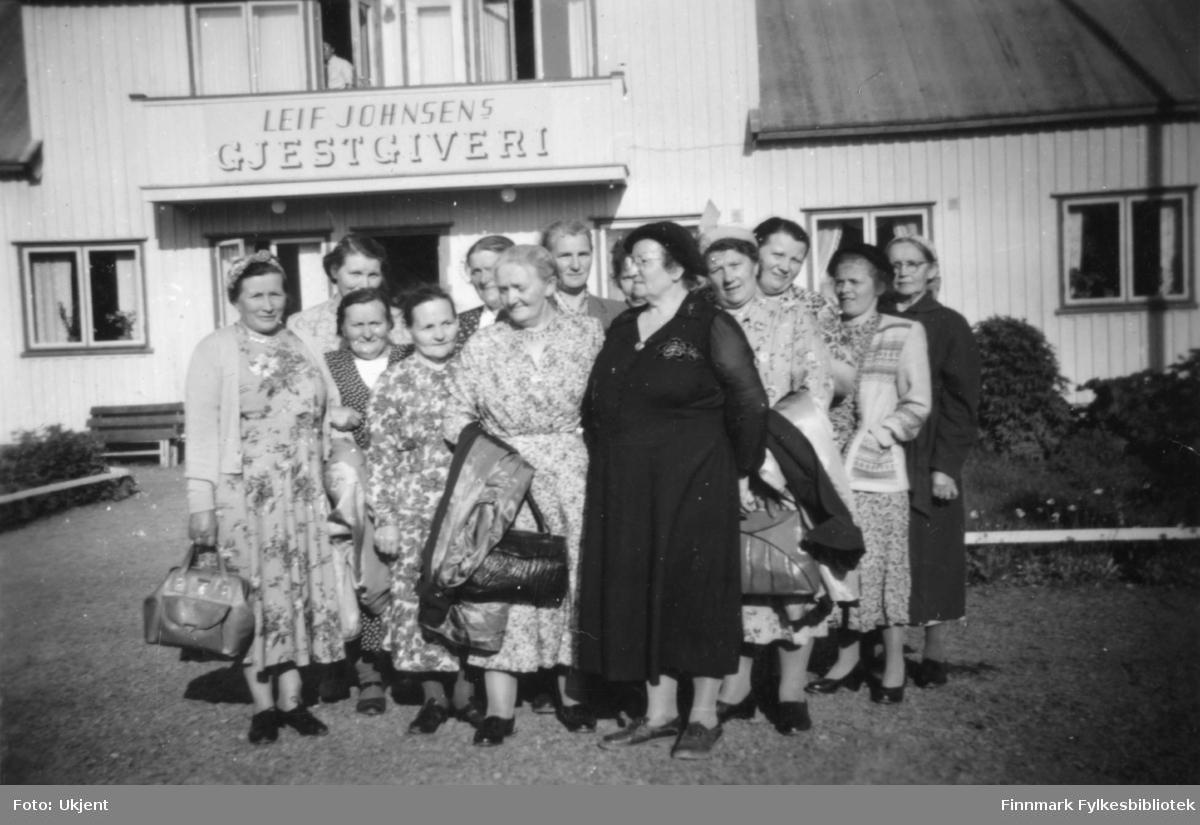 Nesseby husmorslag er ute å reiser. Her poserer de foran Leif Johnsens Gjestgiveri. Leif Johnsens Gjestgiveri var i Rustefjelbma i Tana kommune . Kvinnene har på seg kjoler, skjørt, skjorter, strømpebukser og sko. Enkelte har på seg skaut, andre har briller. Kvinnene holder på vesker. På veggen kan man se vinduer med gardiner i.