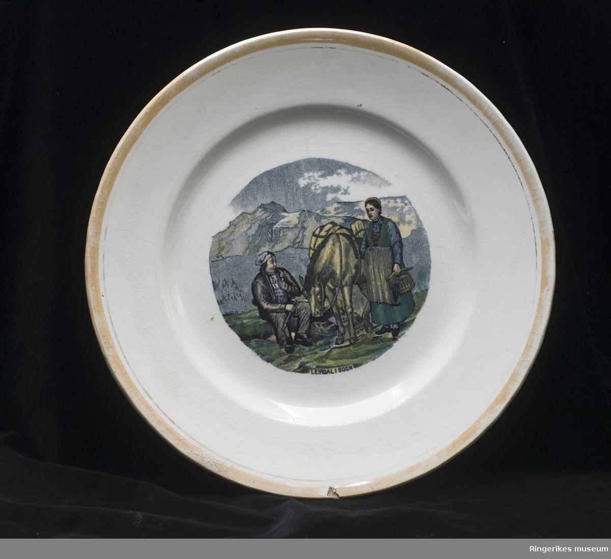 Liten tallerken med motiv  Motivet er muligens inspirert av Adolph Tiedemand  Gitt av frk. Lomsdalen, Skaugstad  Stemplet Egersund Fayanse 1867 - 1876  Motivet er merket LEIRDAL I SOGN