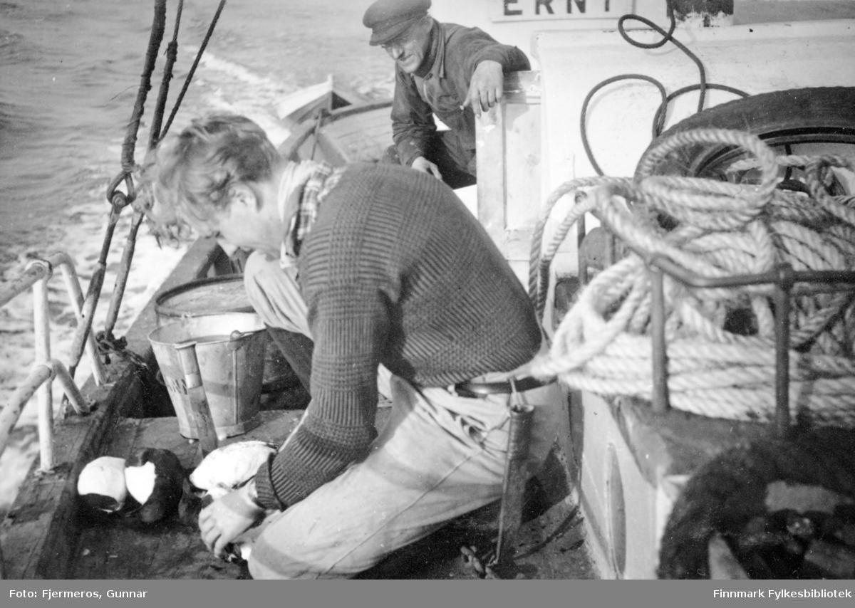 To personer på dekket til en fiskebåt. Personer, sted og båt er ukjent. Bildet er tatt sommeren 1946.