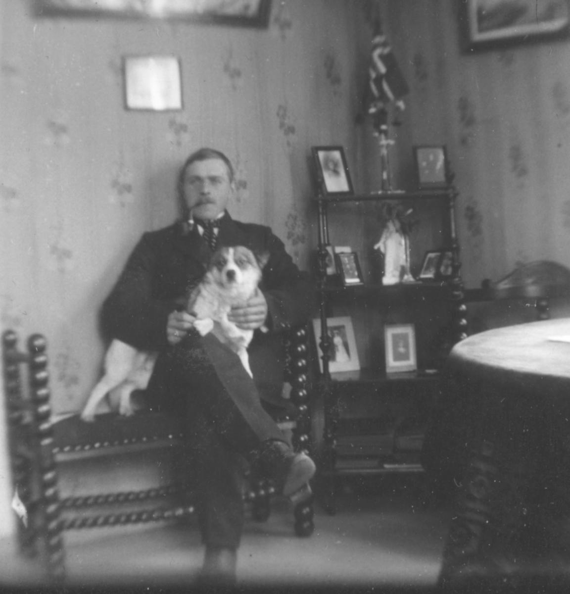 Reidar Håheim poserer for et bilde med hund i fanget. Reidar er kledd i dress og slips og har en pipe i munnen. Bak han kan man se en hylle med fotografier og et norskeflagg.