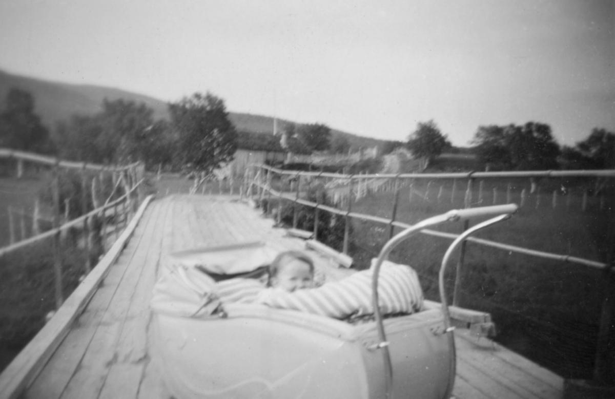 """""""Luftjokbrua ble ferdig i 1927 og det måtte fotograferes. Gerd på 1 år ligger i barnevogna. Bildet er tatt rundt 1930, Gerd er født i 1929. """""""