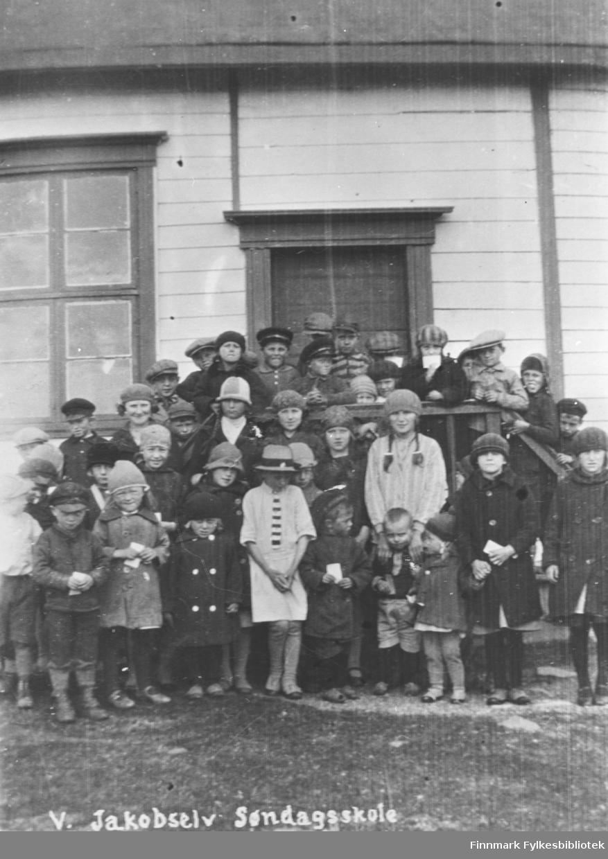 41 barn fotografert ved søndagsskolen i Vestre Jakobselv. En del av ungene står på trappa og de andre foran dem. Ungene er mellon 3-15 år gamle. Alle har hatter eller luer på seg og har en hvit lapp i handen. Bildet muligens tatt før 1930.
