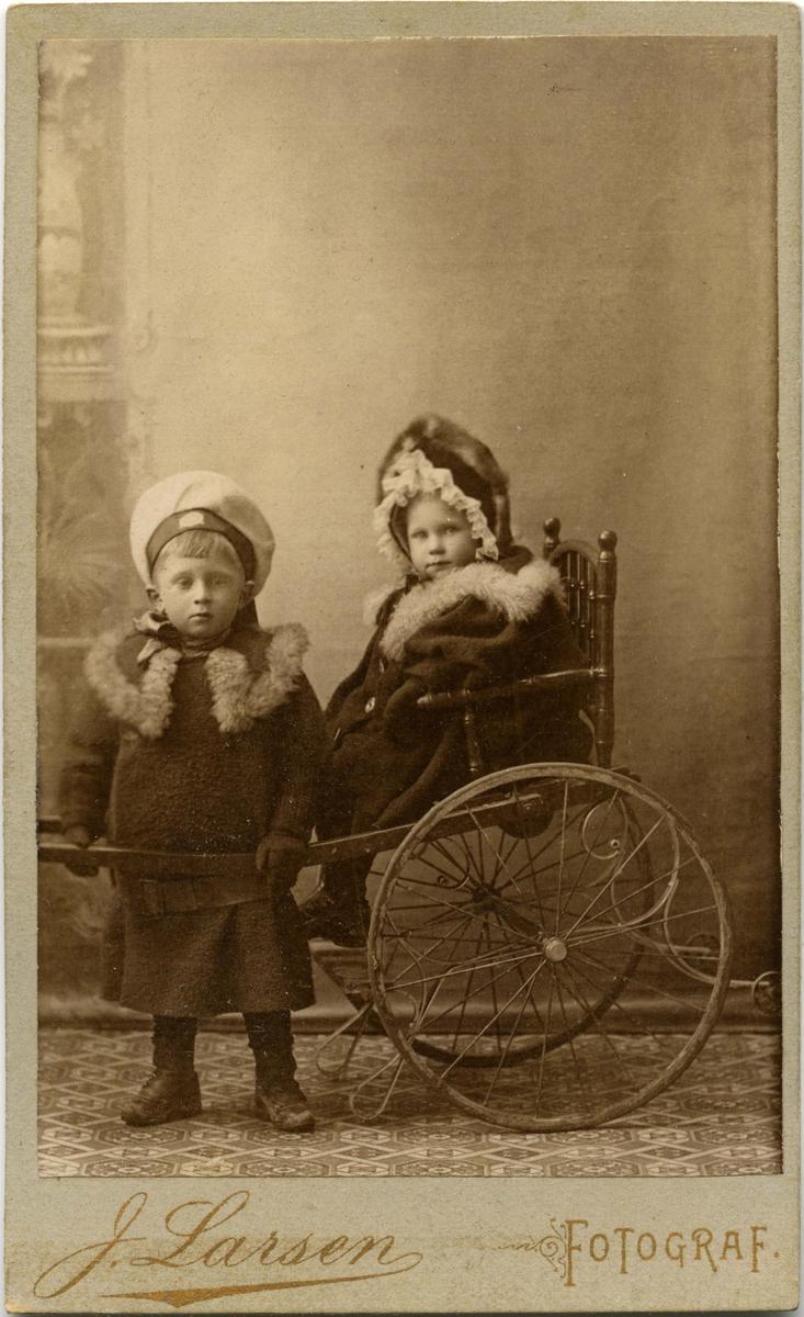 To ukjente barn poserer for et bilde. En liten jente sitter i en trekkbar stol og en gutt står ved siden av.