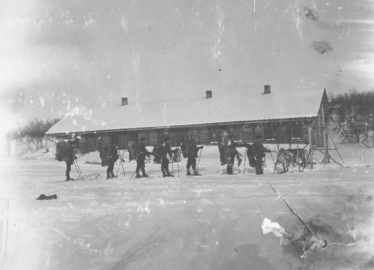 """""""Nyborgmoen."""" Bataljonens menn på skitur. Mennene står på ski med store sekker på ryggen. Framst i rekken kan man se rein."""