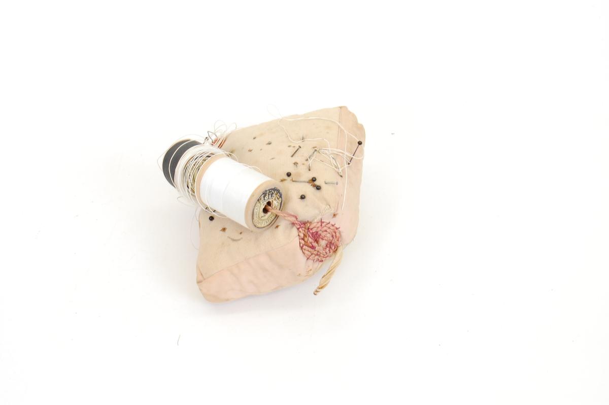 Form: i utgangspunktet en firkantet pute med 6 sider (altså ikke hodepute, men puff-fasong), Ett av hjørnene er sydd på så det er blitt ganske avrundet. En tvinnet tråd går fra dette hjørnet diagonalt over puten til et annet hjørne, og i denne er det festet to trådsneller, svart og hvit. En hempe er også sydd fast i det butte hjørnet. En del knappenåler med og uten stort holde sitter i.