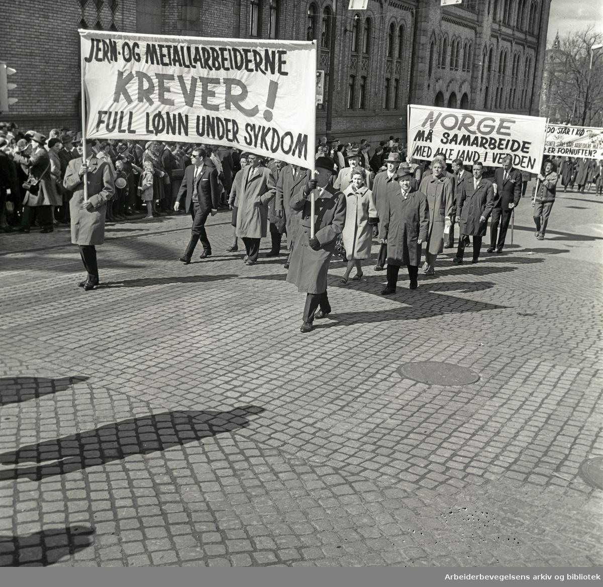1. mai 1964 i Oslo.Demonstrasjonstoget i Karl Johans gate.Parole: Jern og metallarbeiderne krever!.Full lønn under sykdom.Parole: Norge må samarbeide med alle land i hele verden