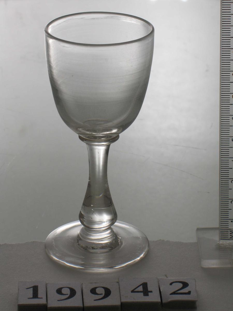 Stetteglass, hetvinsglass. Glass, klart, udekorert. Støpt. Glatt fot, glatt tynn stett,  vaseformet. Rundbunnet klokke med rette sider. smal. smal.