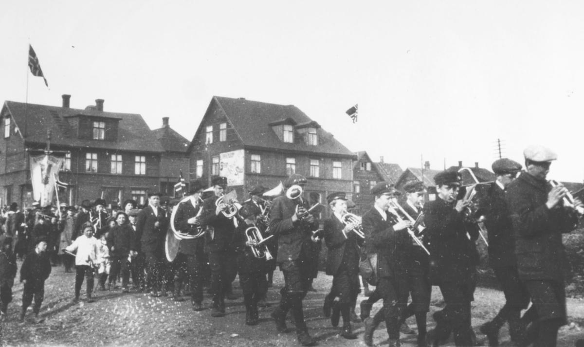17.mai i Kirkenes, 1920. 17.mai-toget med skolekorpset på veg igjennom byen. I bakgrunnen ser vi bolighus, et har reklame- skilt på veggen.