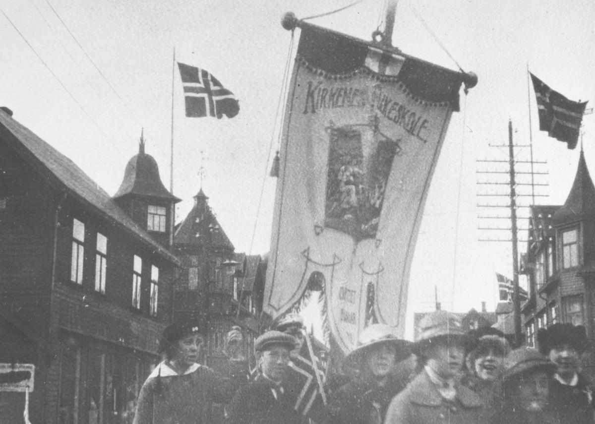 17.mai 1920 i Kirkenes. I forgrunnen åtte mennesker. Over dem er Kirkenes fylkeskole sin fane. I bakgrunnen bygninger med spir.