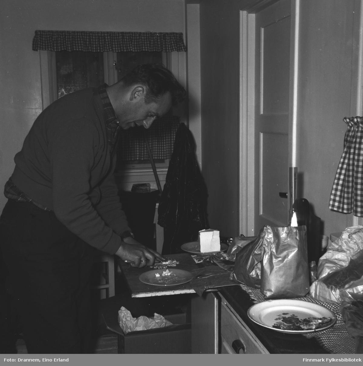 En mann (Jakobsen?)smører brødskviver i kjøkkenet. Bildet er tatt sannsynligvis i Hammerfest
