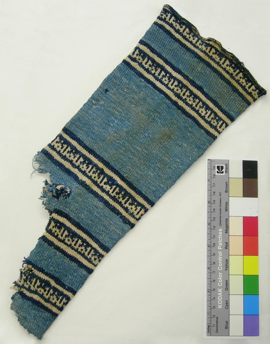 """Del av strumpa från Egypten.   Rundstickad slätstickning. 2-tr bomull, Z-tvinnad. Mellanblå botten med mönsterbårder i mörkblått och vitt. 4 maskor/cm, 7 varv/cm. 5 stycken mönsterbårder, var och en ca 40 mm bred med 3 varv mörkblått, 3 v vitt, 10 v mörkblått med kufisk skrift i vitt, 3 v vitt, 3 v mörkblått. Texten består av ordet """"Allah"""" som upprepas (första konsonanten är utelämnad). Den färg som för tillfället inte används i mönsterstickningen flotterar på avigsidan. Vid garnbyte/skarvning har man lämnat ett par cm långa trådändar som knutits ihop på baksidan. Strumpan är rundstickad från tån och upp. """"Hacket"""" där ett varv övergår till nästa löper längs strumpskaftets ena sida. Strumpans tå och sula saknas helt och endast en liten del av hälen finns kvar i var sida, ca 15 m x 13 varv respektive ca 12 m x 8 varv. Hälen börjar med 3 mörkblå varv, sedan 3 vita, 3 mörkblå, resterande mellanblå. För varje varv har 1 maska minskats på var sida om två rätstickade maskor i var sida = 4 maskor färre för varje varv. Sannolikt har skaftet och foten stickats färdigt först. Sedan har maskor plockats upp och hälen infogats i efterhand."""