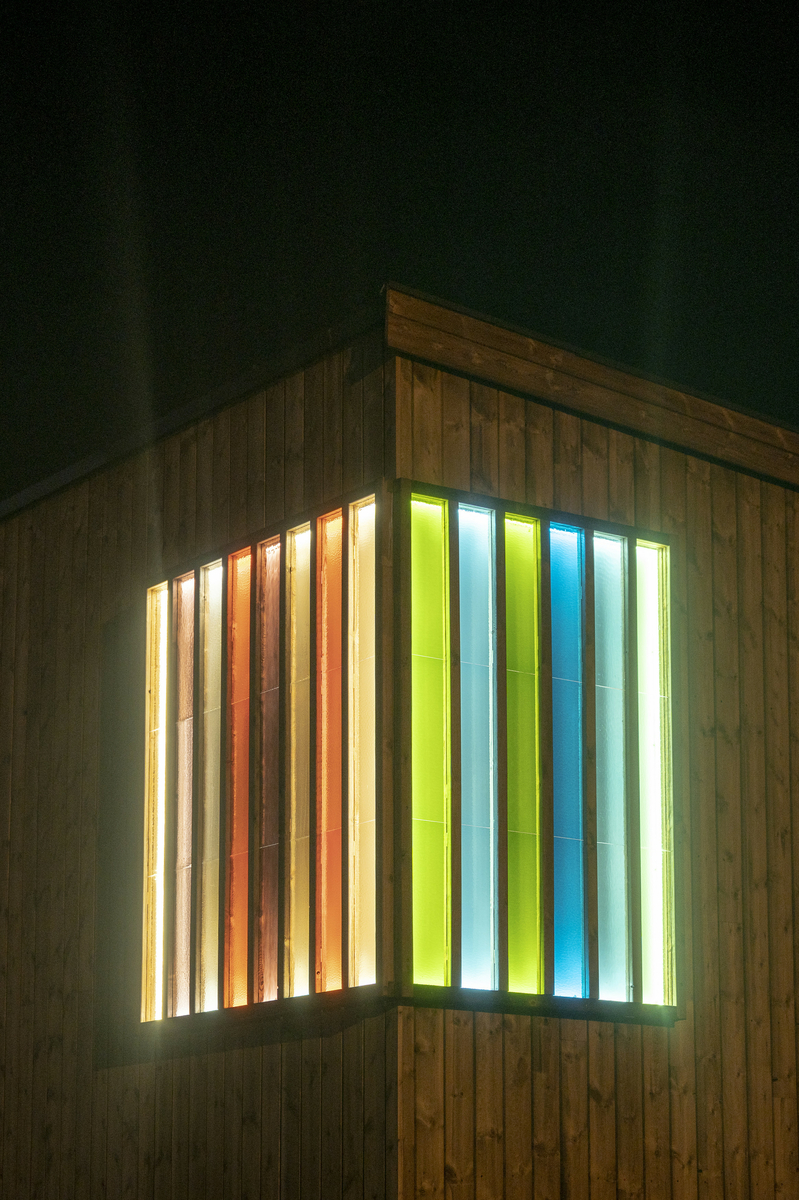 Glass i ulike fargevalører montert som et relieff på skolebyggets fasade. Glasset er lyssatt.