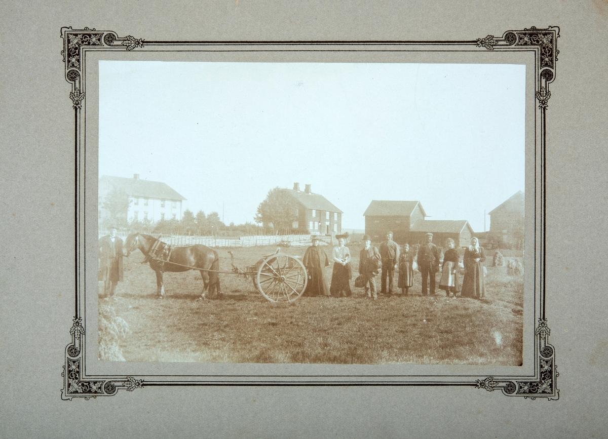 Oversikt over Søndre Enge og Østre Enge i Løten. Gruppe med 9 menesker på tunet. Hest og kjerre.  (kommentar bak på bilde: Dyre og Olga reiser tilbake til Boston, USA)
