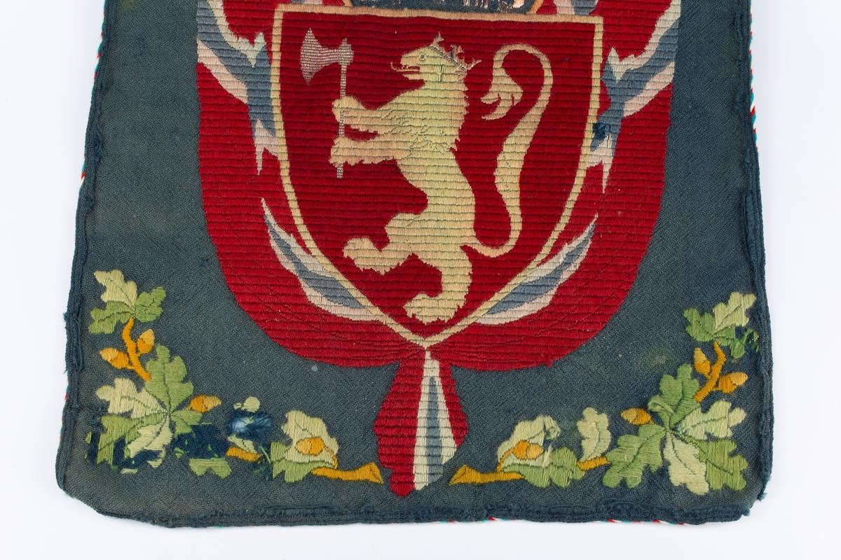 Grå/blå bunn. Klostersøm. Brodert motiv: Det norske riksvåpen og eikeløvmot blå bunn. Kantet med rød, blå og hvit tvunnet snor.