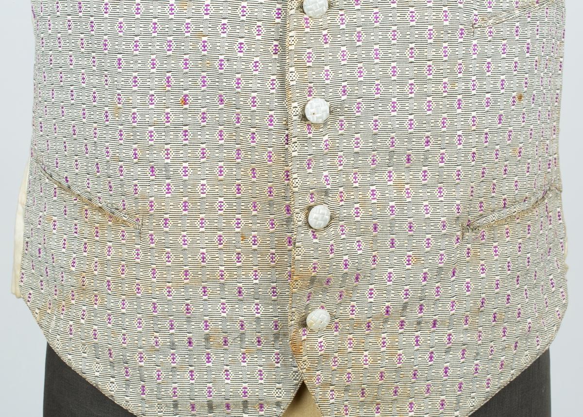 Vest.  Enkeltspent. 5 knapper. Ripsvevet. strukturmønstretr stoff. smale stripe. 5 hvite knapper m Mønsteret dannet av romber i  vertikale striper. Rygg og for i diagonalvevet hvitt stoff. Spensel med spenne i rygg. Fhm.05051 er sløyfe i samme mønster. Bruker og giver ukjent. Ingen produksjonsmerker.