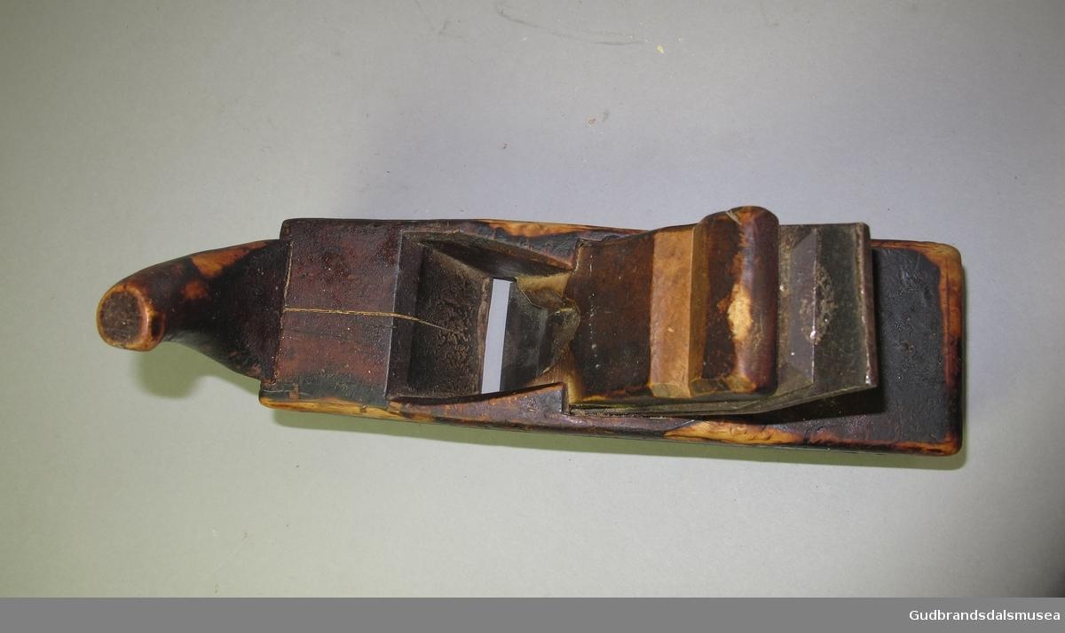 Høvel -  båthøvel.  Høvelstokken er formet oppover i begge ender. Høvelstokken er tjærebredt. Flat tann. Det er felt inn et trestykke i framkant av tanna.
