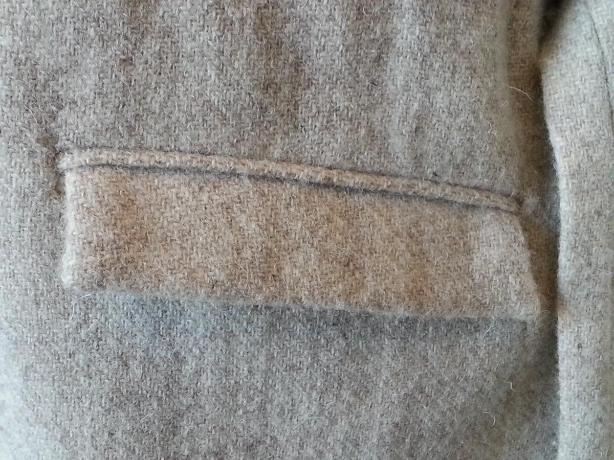 """Knekort, enkeltspent damekåpe av ren ull. Lukket midt foran med 6 tettstilte, små benlignende knapper og knapphull i fronten, og en ekstra knapp øverst. Liten ståkrage, høyere bak. Øvre del av forstykkene kan bøyes til side når knappen ikke er i bruk. Kåpen får da smale """"slag"""". SØLV styler den med slike slag, og lar også ermene ha en liten oppbrett nederst, slik at fôret akkurat kan sees litt i nederkant. Ermene er to-søms, med et ekstra bakstykke. Den bakre sømmen har liten splitt nederst, ca. 4 cm. Kåpen har også 2 bakstykker med et lite innsnitt øverst, midt på skuldersømmen på hver side, søm midt bak og 18,5 cm splitt nederst. Skråstilt, passepoilert lomme med klaff på hver side i hoftehøyde. Beltestropp i i hver side i midjehøyde. Helfôret, med sølvskimrende bånd isydd i sømmen mellom ullen og fôrsilken. Fôret er også sydd inntil nederst. Liten, passepoilert innerlomme på venstre side, noe innsnevret ved at kåpens etikett er påsydd med kryssesting utenpå lommen og noen av stingene går gjennom. Langt knyttebelte i tweed, opprinnelig løsthengende , men nå festet midt bak av museets skredderutdannede assistent."""
