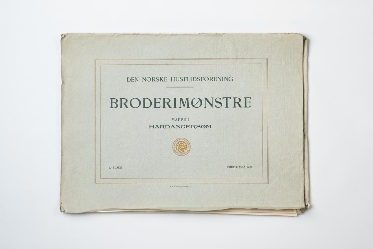 """Mapp av papper med mönster på hardangersöm (vitbroderi). Häftet innehåller 10 blad i form av tryckta fotografier i svart-vitt. På mappens framsida tryckt text: """"DEN NORSKE HUSFLIDSFORENING BRODERIMØNSTRE MAPPE 1 HARDANGERSØM CHRISTIANIA 1906"""". Mappens pris 3.00 kr och enkelt blad 0,35 kr. Tryck: W.C. Fabritius & Sønner A/S."""