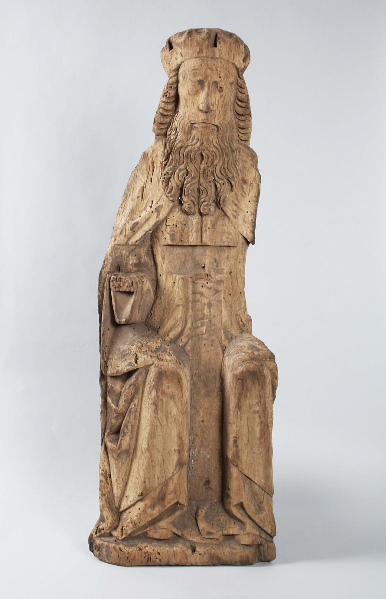"""Träskulptur """"Nådastolen"""", 1400-tal, mycket defekt (träbortfall); all färg borta. Sittande frontalt; båda armarne saknas; krucifixet saknas; värkar besynnerligen platt. Maskstungen. Proveniens Tärby kyrka.  Nådastolen är ett motiv som uppkommer på 1100-talet men som i den kyrkliga konsten under 1400-talet får ett rejält uppsving. Motivet, som är en treenighetsframställning visande fadern, sonen och den helige ande, finns återgivet i flera olika media, till exempel i muralmålningar, på smycken och i altarskåp. Det visar hur Gud, iförd krona eller påvetiara, sitter på en tronstol och håller upp och visar fram den döde Jesus för betraktaren med den Helige Andes duva svävande bredvid eller sittande på korset. (Historiska museet)  Tärby kyrka härstammar troligen från 1200-talet. Under 1700-talet renoverades kyrkan och de gamla målningarna som då gjordes, målades över under 1800-talet. Kyrkan vilar förmodligen på en forntida offerplats, som var centrum för en kulturbygd sedan årtusenden. (Svenska kyrkan)"""