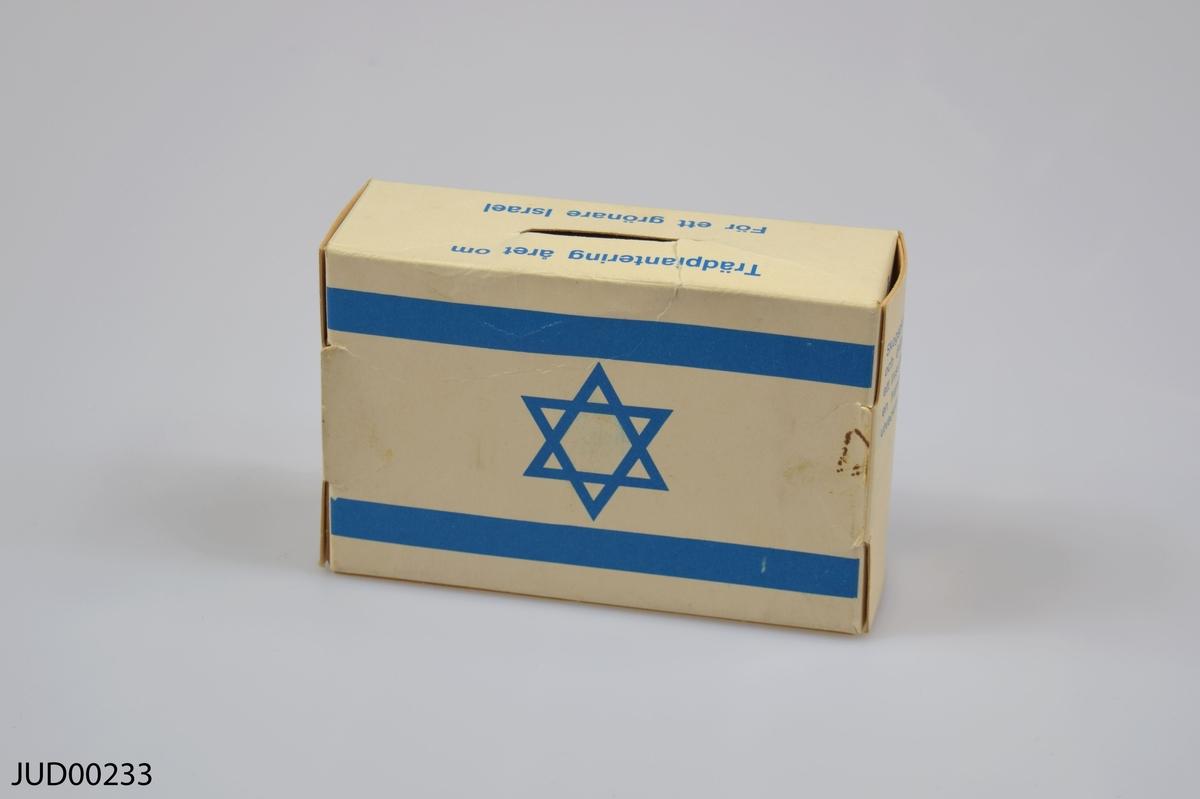 """Insamlingsbössa, tillverkad av papper. Dekorerad med Israels flagga samt en karta över landet. Följande text står på bössan:  """"Trädplantering året om. För ett grönare Israel""""  """"Keren Kajemet - Judiska Nationalfronden i Sverige. Nybrogatan 19, 114 39 Stockholm. Telefon 08-618686, postgiro 150376-2""""  """"Skogsplatering och dränering är ett livsvillkor för en framgångsrik utveckling av Israel""""  """"Keren Kajemet har till uppgift att i Israel förbättra marken och göra den lämplig för kolonisation samt att täcka bergskullar och ökentrakter med träd"""""""
