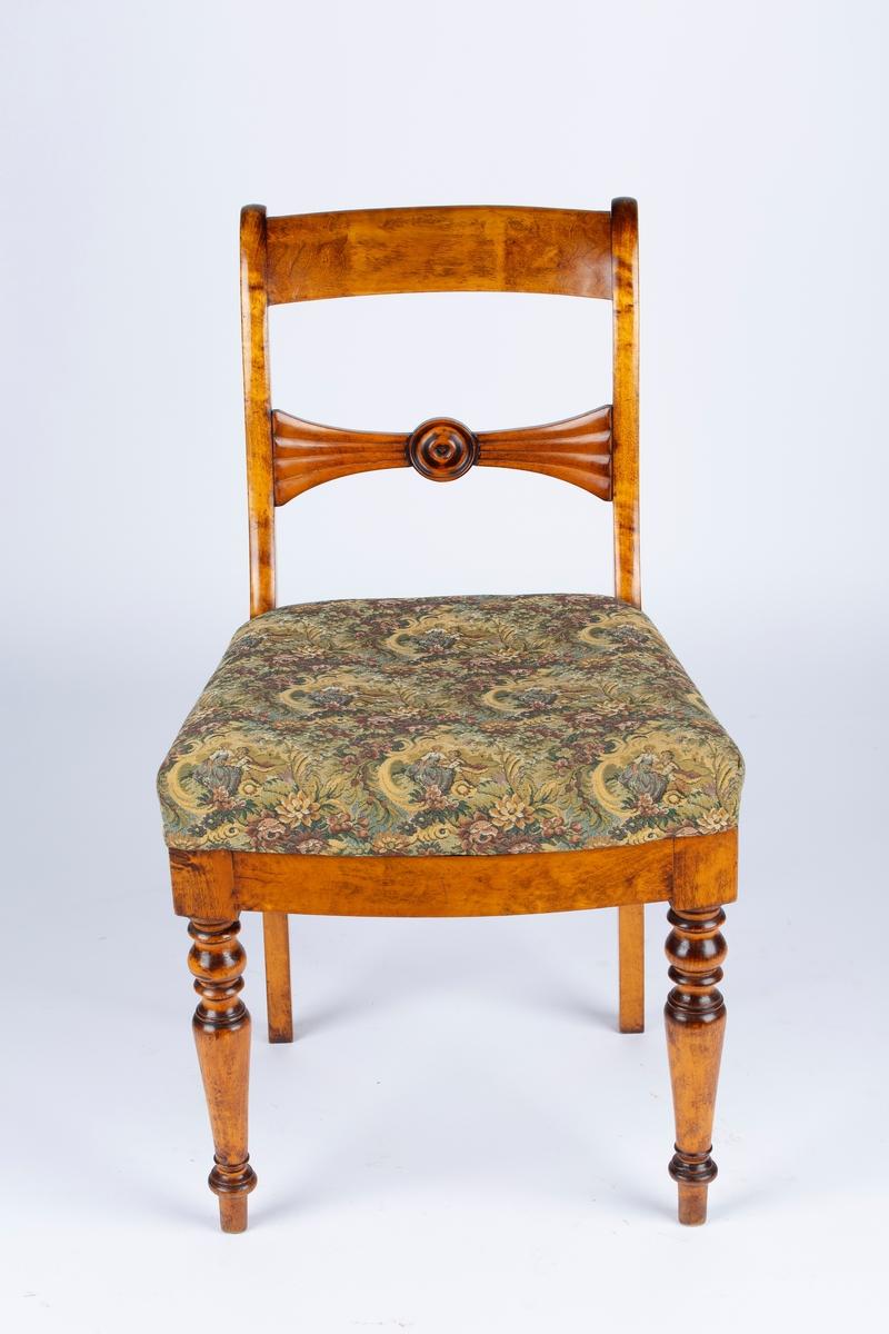 Spisestuestol uten armlener. Løst sete med stopp, og trekk med blomster og mennesker. Setestoffet er spikret fast til rammen. Tegn på at setet er trukket om. En tapp i rammen og et hull på undersiden av setet holder det på plass. Tappen er ikke hel. Ved hullet kan man skimte et annet tekstil i en lilla og rosa farge. Dreide stolben foran og utstkjæringer i ryggen. Svak bøy på stolbena bak. Tverrbrett med innfelt rosett. Biedermeierstil. Øverst til venstre på stolryggen ser det ut til å ha vært en reparasjon. Tappen som stikker ut, ser ut til å ha blitt limt på igjen.