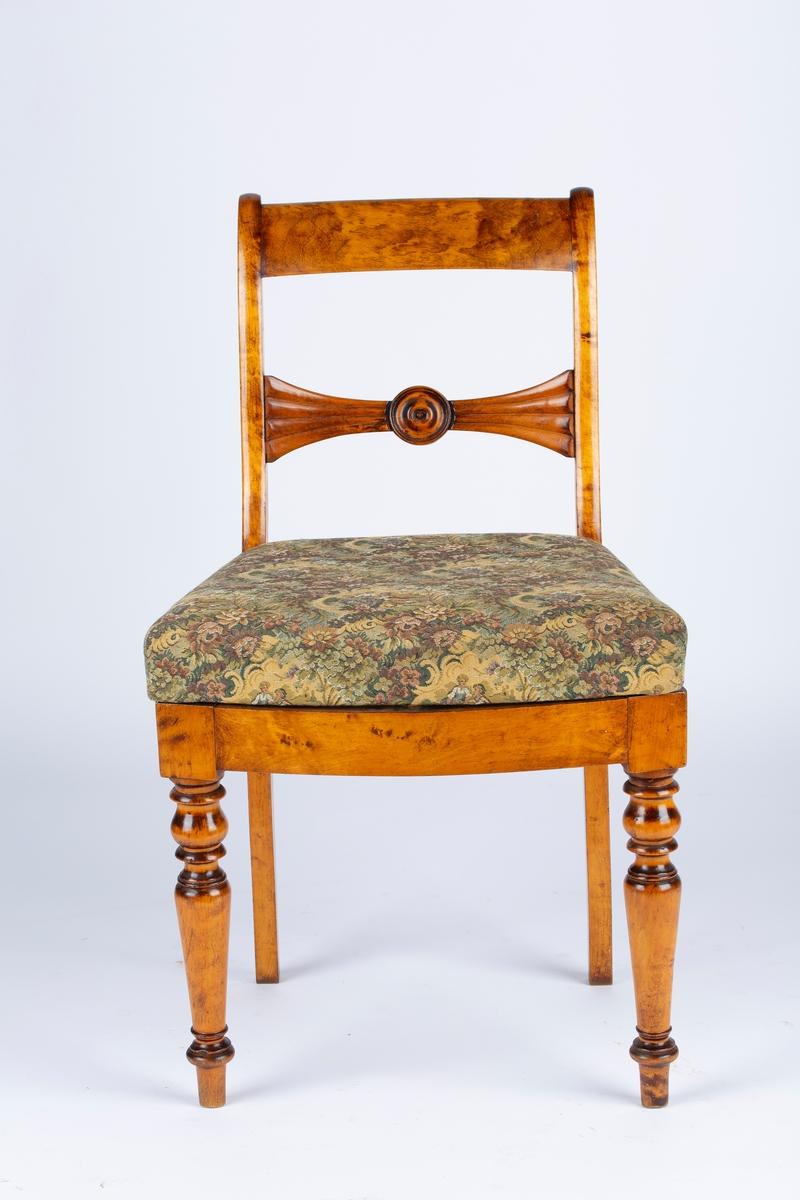 Spisestuestol uten armlener. Løst sete med stopp, og trekk med blomster og mennesker. Setestoffet er spikret fast til rammen. Tegn på at setet er trukket om. I kantene under setet kan man skimte et annet tekstil i en lilla og rosa farge. En tapp i rammen og et hull på undersiden av setet holder det på plass. Dreide stolben foran og utstkjæringer i ryggen. Svak bøy på stolbena bak. Tverrbrett med innfelt rosett. Biedermeierstil. Øverst til venstre på stolryggen ser det ut til at tappen som stikker ut har blitt limt på.