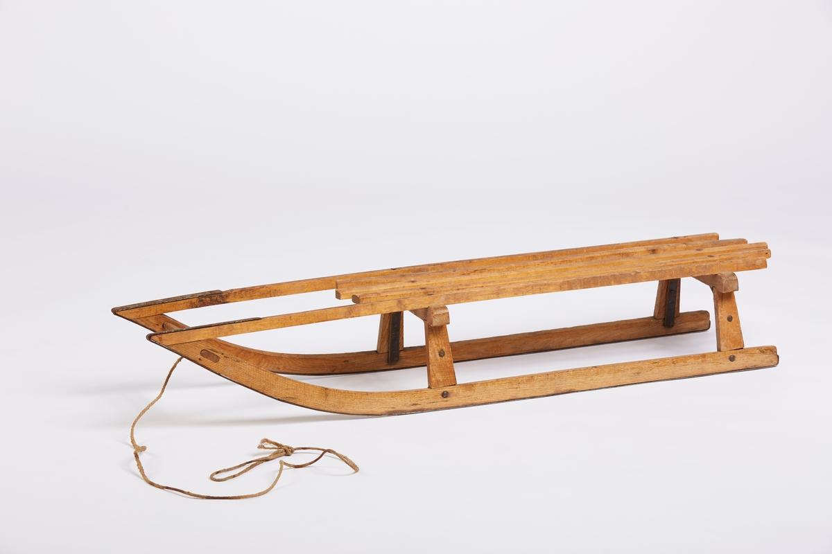 En tradisjonell trekjelke med påskrudde stålbånd under meiene. 5 spiler i setet. Kjelken har trekksnor med løkke.