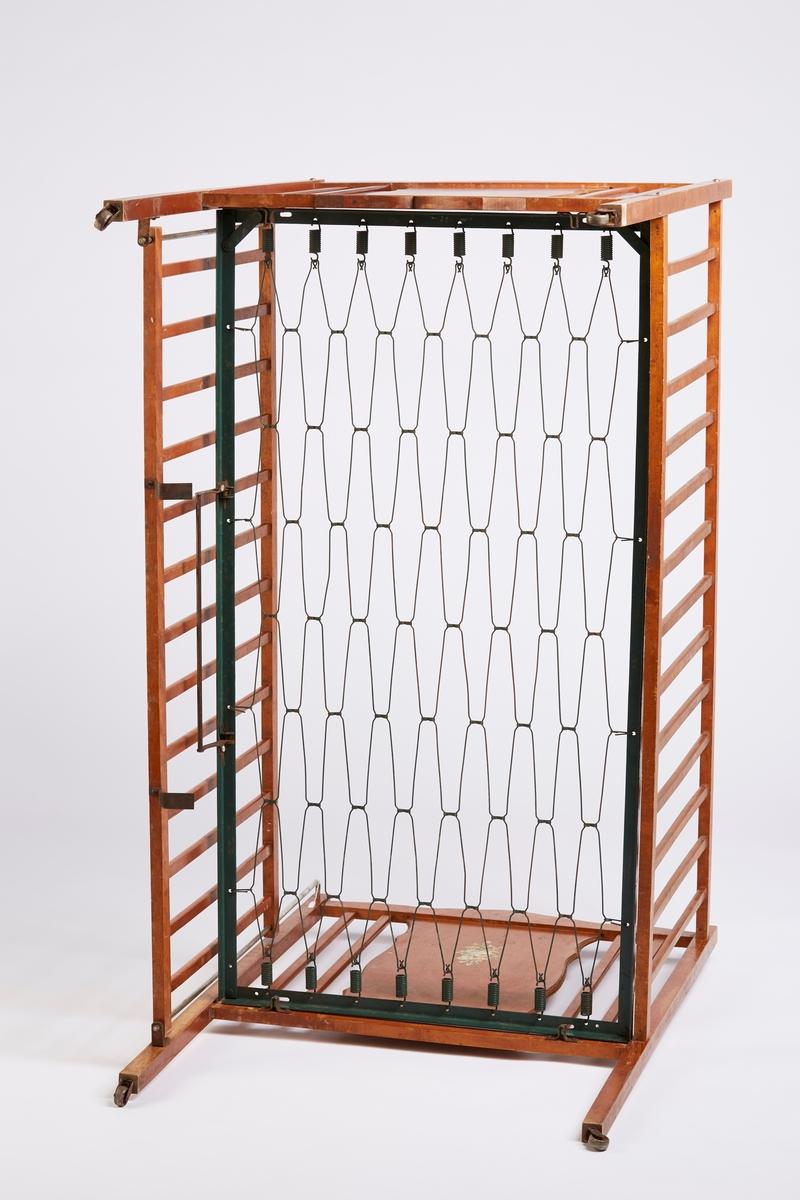 Sprinkelseng i løvtre. Profilskårne dekorfelt i sengegavlene. Metallhjul. Oblatdekor.  Sengebunn i metall, ramme og fjærer. Det ligger ved en pose med ekstra deler: To låseskruer med fjærer, to skruer uten mutter.