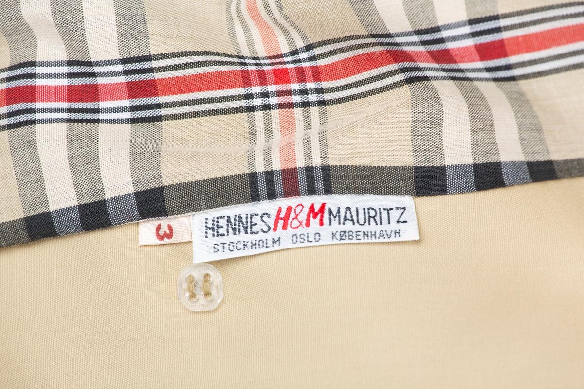 """A: Kåpe Konfeksjon. Store slag og krage. Dobbeltknappet 3 sett knapper. Belte med spenne. Skulderklaffer. Håndleddstrammer. Lengden sekundært redusert, aklippet og lagt opp. Rutet for """"Burberry""""-ruter  B: Belte med spenne, bredde 5 cm.  Kjøpt til pyntet bruk hos Hennes&Mauritz i Oslo 1976. Merke, MODESSA."""