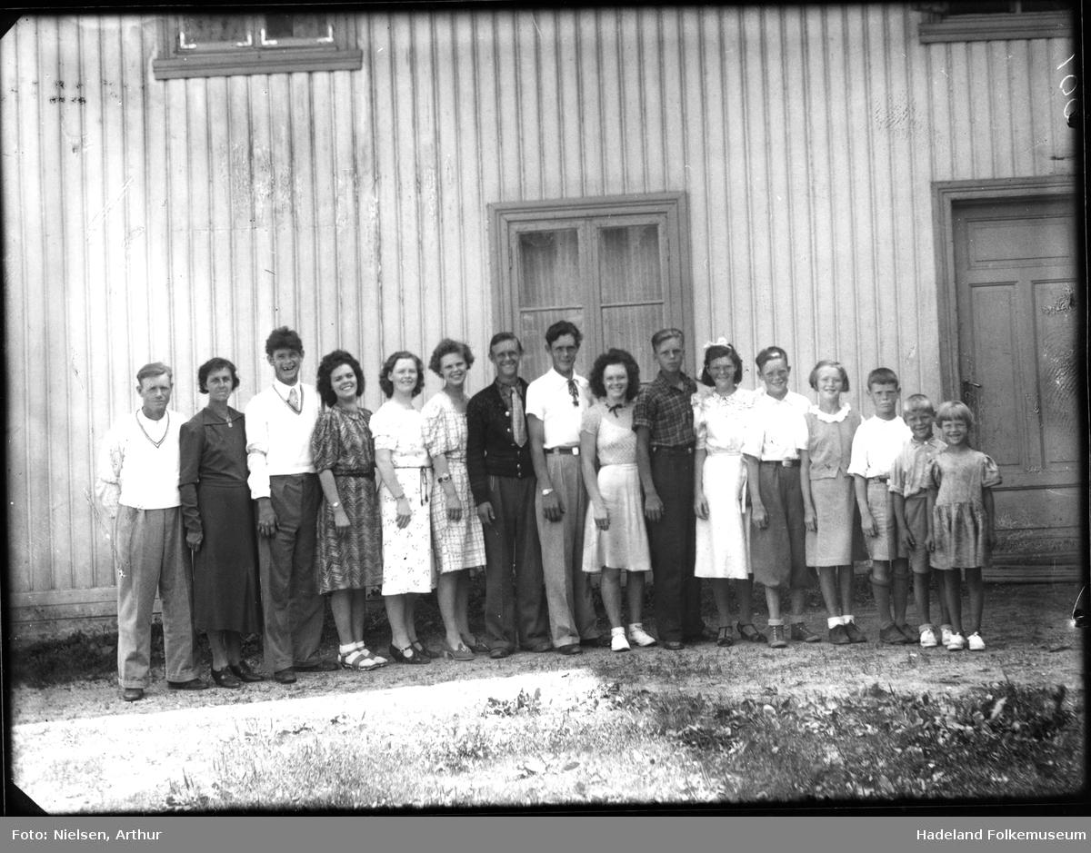 Familien Bakken, på seksten personer står utenfor et hus.